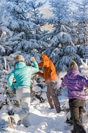 snowball: Snowball fight winter friends having fun playing in snow outdoors Stock Photo