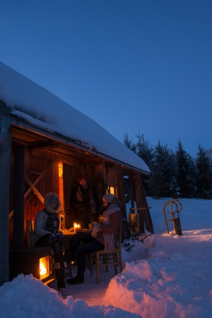Sunset winter cottage friends enjoying evening in snow countryside photo