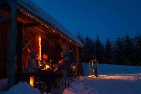 Evening winter cottage friends enjoy hot drinks in snow countryside