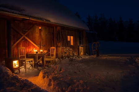 Cozy wooden cottage in dark winter forest snow countryside photo