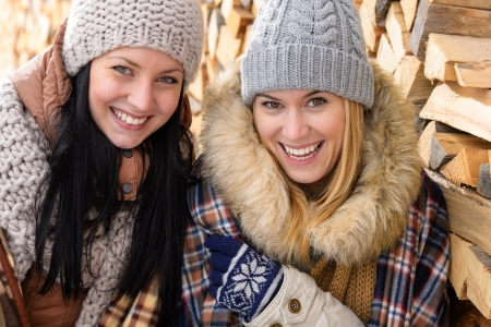 Two smiling friends in winter jackets countryside wooden logs background photo