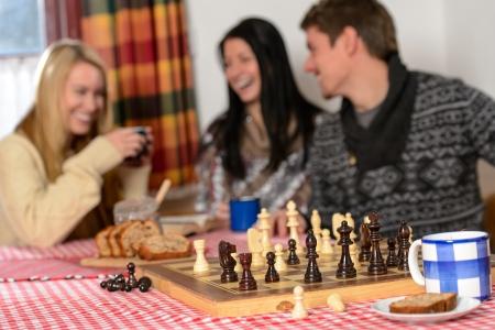 jugando ajedrez: Jugar ajedrez acogedoras amigos chalet de invierno riendo pasar vacaciones Foto de archivo