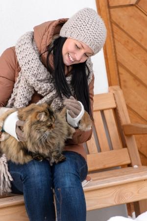 okşayarak: Kış yazlık okşayarak kedi dışında bankta oturan genç kadin
