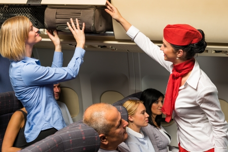 stewardess: Friendly flight attendant helping passenger to put luggage cabin compartment Stock Photo