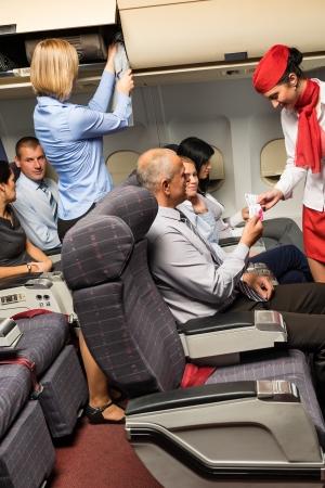 Flugbegleiterin Kontrolle der Fahrscheine in Flugzeug-Kabine