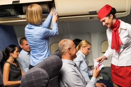 Hôtesse de l'air chèque billet du passager dans la cabine de l'avion sourire Banque d'images
