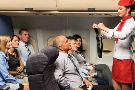 cinturon de seguridad: Seguridad Asistente de vuelo de demostración de fijación del cinturón de seguridad de la cabina del avión de pasajeros