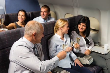 Airplane cabin businesspeople toasting with champagne flight travel passenger Banque d'images