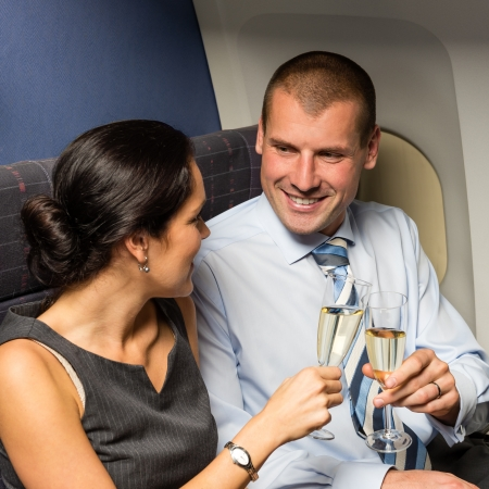 Flight cabin business partners toasting champagne airplane travel passengers photo
