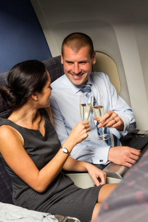 Smart couple business travel by airplane toasting champagne passengers flight photo