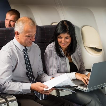 Businesspeople working on computer during flight airplane cabin passenger travel photo