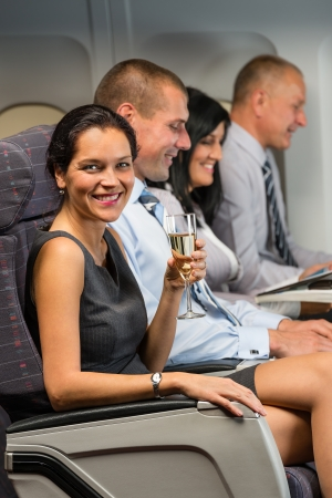 Young businesswoman enjoy flight glass champagne airplane cabin travel passenger photo