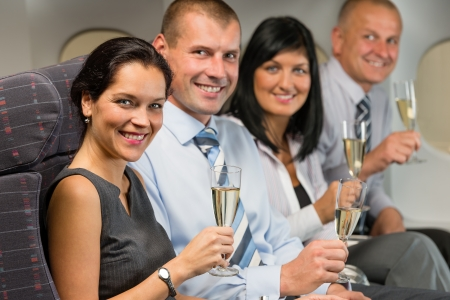 Business people flying airplane drink champagne smiling at camera photo