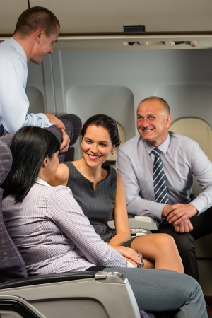 Business people passengers flying airplane talking travel flight cabin photo