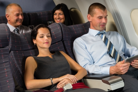 Airplane passengers relax during flight cabin sleep businesspeople