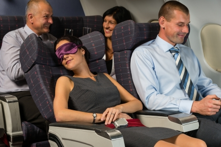 Business woman sleep during night flight airplane cabin passengers photo