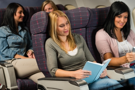 Leisure travel young woman passenger read book airplane cabin flight