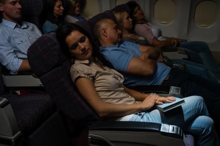 sitting people: Flight passengers sleeping plane cabin night travel Stock Photo
