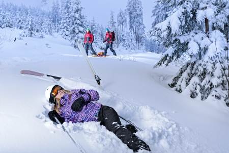 injured woman: Skier after accident waiting for mountain rescue lying in snow
