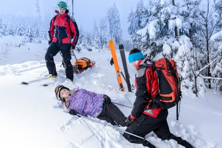 accident at work: Rescue ski patrol help injured woman skier lying in snow