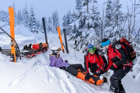 Ski équipe de patrouille de sauvetage femme skieur avec une jambe cassée