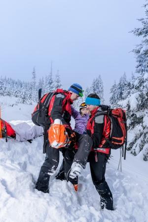 スキー場のパトロールの救助の担架で負傷した女性スキーヤーを運ぶ