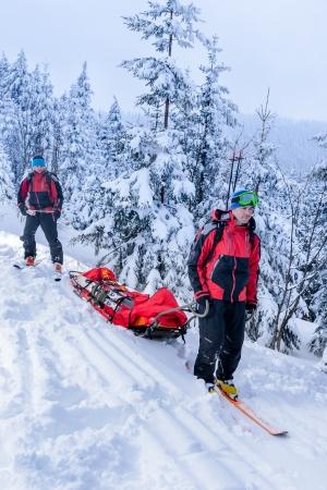 Ski patrol members carry injured skier downhill rescue stretcher Stock Photo