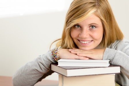 Smiling student teenager leaning head on stack of books