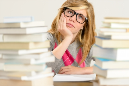Bored student girl between stack of books looking up glasses photo