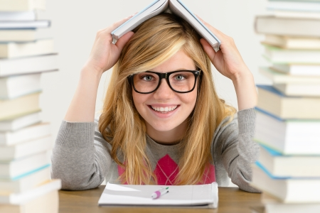 Smiling student teenager holding book over her head sitting desk Stock Photo