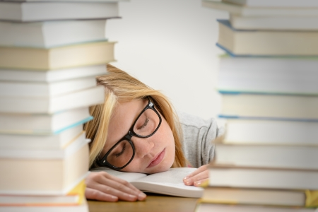 Student girl sleeping on desk between stacks of books photo