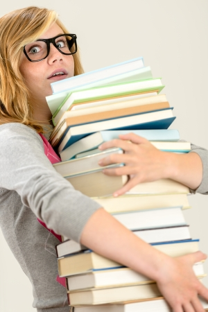 Worried student girl carry stack of books wear glasses photo