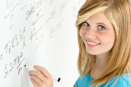 глядя на камеру: Улыбаясь студент девочка-подросток письменной математике белая доска, глядя камеры Фото со стока