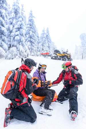 Ski patrol team rescue woman skier with broken arm photo