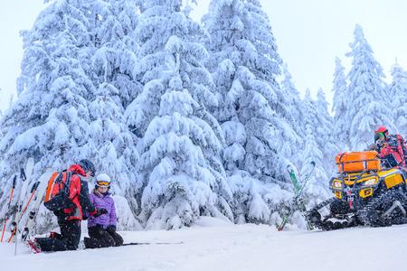 Ski patrol helping woman with broken arm rescue quad photo