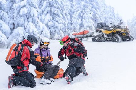 Ski patrol team rescue woman skier with broken arm photo