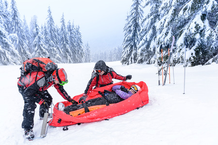 patrol: Ski patrol with rescue sled helping injured woman snow forest