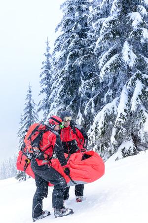 Ski patrol carry injured person skier in rescue stretcher snow photo