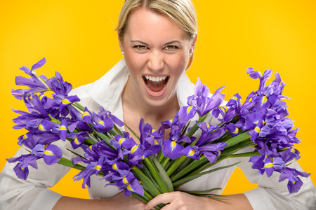 Woman with spring iris flower roar on yellow background photo