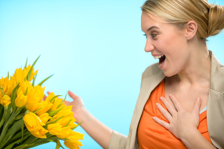 Surprised woman receive bouquet of yellow tulip flowers spring photo