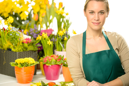 Potted plants: Florist with spring potted flowers colorful looking at camera Stock Photo