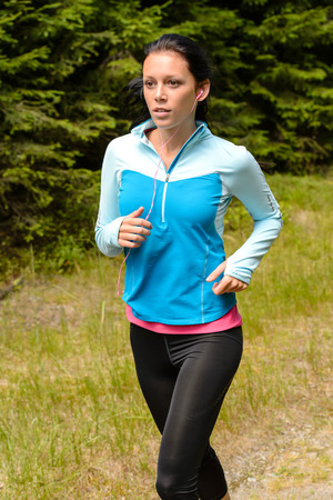 Sportive woman running  through meadow in countryside close-up Stock Photo - 25955542