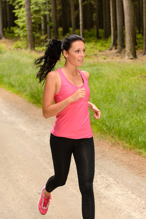 Sportive woman running through forest on summer training day Stock Photo - 25955545