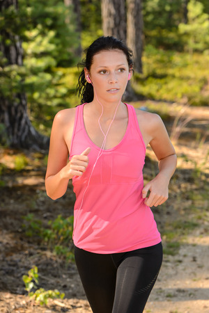 Woman running in the countryside training with earphones photo