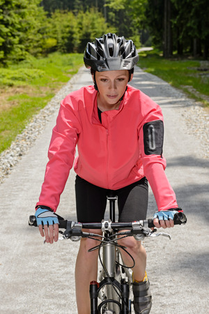 Woman riding mountain bike on sunny countryside cycling path photo