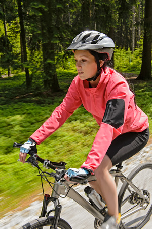 Woman mountain biking in forest motion blur training race photo