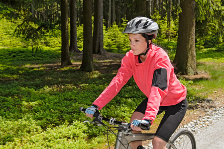 Woman mountain biking in forest on sunny day cycling path photo