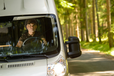 Postal delivery courier in van on his way delivering package photo