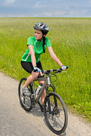 Woman riding her bicycle on countryside road sunny day Stock Photo - 26539472