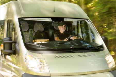 パッケージを配布する貨物バンを運転郵便配達宅配便の男 写真素材